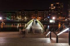 Φωτισμένη γέφυρα ποδιών πέρα από τη βόρεια αποβάθρα στο Canary Wharf τή νύχτα Στοκ εικόνα με δικαίωμα ελεύθερης χρήσης