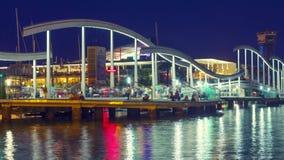 Φωτισμένη γέφυρα στη μαρίνα Vell λιμένων τη νύχτα ελαφρύ ύδωρ αντανακλάσεων απόθεμα βίντεο