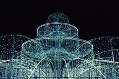 Φωτισμένη πηγή που διακοσμείται με τις γιρλάντες, τους εορταστικούς φωτισμούς και τα φω'τα Χριστουγέννων, στοιχεία διακοσμήσεων τ στοκ εικόνα