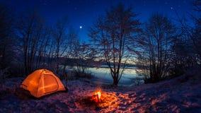 Φωτισμένη σκηνή στο χειμερινό στρατόπεδο από τη λίμνη τη νύχτα στοκ φωτογραφίες