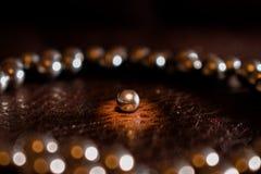Φωτισμένη σφαίρα μετάλλων από το ρουλεμάν στον κύκλο άλλων σφαιρών Στοκ Φωτογραφίες