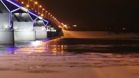 Φωτισμένοι νύχτα γέφυρα και ποταμός με τον πάγο τη νύχτα απόθεμα βίντεο