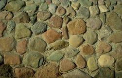 φωτισμένος ανασκόπηση ήλιος πετρών βράχου Τοίχος πετρών Μικρές πέτρες στον τοίχο Κλείστε επάνω του τοίχου με τις πέτρες Στοκ Εικόνες