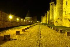 Φωτισμένος δρόμος πετρών μεταξύ των τοίχων και των πύργων του κάστρου του Carcassonne στοκ εικόνες