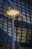 Φωτισμένος λαμπτήρας οδών ενάντια στο κτίριο γραφείων τη νύχτα στοκ εικόνα