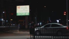 Φωτισμένος πίνακας διαφημίσεων Η διαφημιστική αντιπροσωπεία διαφημίζει τις υπηρεσίες της στη φωτεινή επίδειξη κυλίνδρων Οδός βραδ απόθεμα βίντεο
