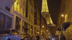 Φωτισμένος πύργος του Άιφελ τη νύχτα, άποψη από τη στενή οδό με τα υψηλά κτήρια απόθεμα βίντεο