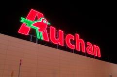 Φωτισμένο λογότυπο Auchan στην υπεραγορά στο Γντανσκ Το Auchan είναι διεθνές αλυσίδα σουπερμάρκετ στοκ φωτογραφίες