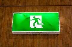 Φωτισμένο πράσινο σημάδι εξόδων που αναστέλλεται από το ανώτατο όριο Στοκ φωτογραφίες με δικαίωμα ελεύθερης χρήσης