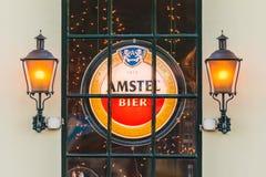 Φωτισμένο σημάδι με το ολλανδικό λογότυπο μπύρας Amstel πίσω από ένα παράθυρο Στοκ φωτογραφία με δικαίωμα ελεύθερης χρήσης