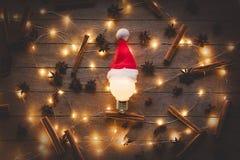Φωτισμοί και βολβός Χριστουγέννων στο καπέλο Άγιου Βασίλη στοκ εικόνες