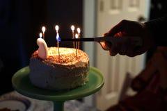 Φωτισμός των κεριών κέικ γενεθλίων Στοκ φωτογραφία με δικαίωμα ελεύθερης χρήσης