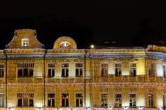 Φωτισμός Χριστουγέννων σε ένα 19ο κτήριο αιώνα Οι τοίχοι που διακοσμούνται όλοι με τις γιρλάντες Στοκ Εικόνες