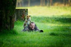 Φωτογράφος άγριας φύσης που κρύβεται στη χλόη με την περίεργη αλεπού στην πλάτη του Στοκ Εικόνες