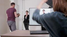 Φωτογράφος και πρότυπο που λειτουργούν στην επαγγελματική φωτογραφία που τίθεται στο στούντιο απόθεμα βίντεο