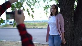 Φωτογράφος κοριτσιών, που φωτογραφίζει μια γυναίκα υπαίθρια, στο πάρκο μια νεφελώδη ημέρα απόθεμα βίντεο