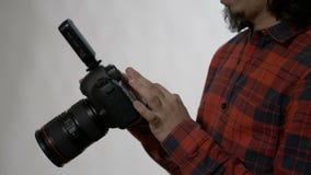 Φωτογράφος με τη γενειάδα που ελέγχει και που διαγράφει τις φωτογραφίες που έκανε σε ένα στούντιο με την επαγγελματική κάμερα dsl απόθεμα βίντεο