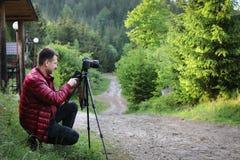 Φωτογράφος με τη κάμερα στο τρίποδο που πυροβολεί ένα τοπίο στο δάσος Στοκ Εικόνες