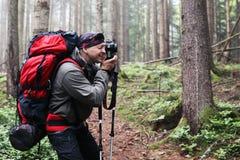 Φωτογράφος με τη κάμερα στο τρίποδο που πυροβολεί ένα τοπίο στο δάσος Στοκ εικόνες με δικαίωμα ελεύθερης χρήσης