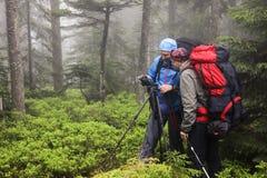 Φωτογράφος με τη κάμερα στο τρίποδο που πυροβολεί ένα τοπίο στο δάσος Στοκ εικόνα με δικαίωμα ελεύθερης χρήσης
