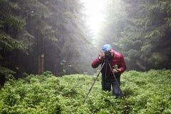 Φωτογράφος με τη κάμερα στο τρίποδο που πυροβολεί ένα τοπίο στα fores Στοκ εικόνες με δικαίωμα ελεύθερης χρήσης