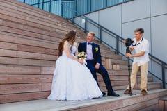 Φωτογράφος με το νεόνυμφο και τη νύφη Στοκ φωτογραφία με δικαίωμα ελεύθερης χρήσης