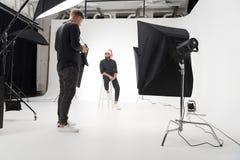 Φωτογράφος που εργάζεται στο στούντιο με το πρότυπο στοκ φωτογραφία με δικαίωμα ελεύθερης χρήσης