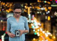 φωτογράφος που παίρνει μια φωτογραφία με την εκλεκτής ποιότητας κάμερα background blurred city lights Στοκ Φωτογραφία