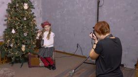 Φωτογράφος που παίρνει το κορίτσι εφήβων εικόνων με το φανάρι στο υπόβαθρο χριστουγεννιάτικων δέντρων απόθεμα βίντεο