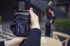 Φωτογράφος που πυροβολεί μια όμορφη γυναίκα brunette σε έναν περίπατο στην ΕΕ Στοκ Φωτογραφίες
