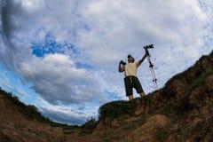 Φωτογράφος που στέκεται το άσπρο υπόβαθρο σύννεφων Στοκ εικόνα με δικαίωμα ελεύθερης χρήσης