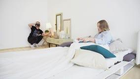 Φωτογράφος που φωτογραφίζει το πρότυπο που βρίσκεται στο κρεβάτι MEDIA Βλαστοί φωτογράφων, που χρησιμοποιούν το φως του λαμπτήρα, απόθεμα βίντεο