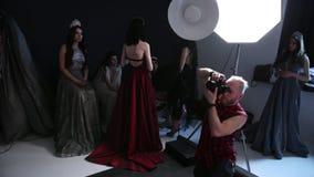Φωτογράφος που φωτογραφίζει το πρότυπο κοριτσιών, brunette, σε ένα μπλε φόρεμα, στο στούντιο απόθεμα βίντεο