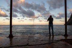 Φωτογράφος που φωτογραφίζει το χρυσό ηλιοβασίλεμα από την αποβάθρα στοκ εικόνες