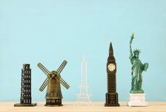 φωτογραφία έννοιας μερικά από το παγκοσμίως διάσημο ορόσημο για το ταξίδι, μικρά αγάλματα πέρα από τον ξύλινο πίνακα στοκ εικόνα