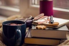 Φωτογραφία αντικειμένου Στο windowsill βιβλίο, σημειωματάριο, περίπτωση γυαλιών, μπισκότα, termoz και κούπα με το θερμαμένο κρασί στοκ φωτογραφίες
