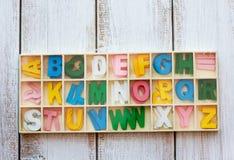 Φωτογραφία αποθεμάτων - ζωηρόχρωμο ξύλινο αγγλικό αλφάβητο που τίθεται στο ξύλινο κιβώτιο Στοκ Εικόνες