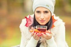 Φωτογραφία αποθεμάτων: Νέα ελκυστική γυναίκα που κρατά το διαθέσιμο καυτό κόκκινο τσάι Χαλάρωση στη φύση φθινοπώρου με το καυτό τ Στοκ φωτογραφία με δικαίωμα ελεύθερης χρήσης