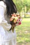 Φωτογραφία αποθεμάτων: Νύφη που κρατά την ανθοδέσμη της πίσω από την πίσω Στοκ Εικόνα