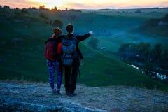Φωτογραφία από το πίσω μέρος του αγκαλιάσματος του άνδρα και της γυναίκας τουριστών με τα σακίδια πλάτης στο βουνό στοκ φωτογραφίες με δικαίωμα ελεύθερης χρήσης