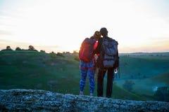Φωτογραφία από το πίσω μέρος του αγκαλιάσματος του ζεύγους των τουριστών στο βουνό στοκ φωτογραφίες