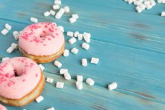 Φωτογραφία δύο donuts που καλύπτονται με τη ρόδινη τήξη σε ένα μπλε ξύλινο υπόβαθρο με μια θέση για μια επιγραφή Εύγευστος στοκ εικόνα με δικαίωμα ελεύθερης χρήσης