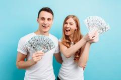 Φωτογραφία ενός ευτυχούς νέου ζεύγους ερωτευμένου, του άνδρα και της γυναίκας, που ντύνονται κρατώντας τα χρήματα στα χέρια τους, στοκ εικόνα