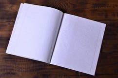 Φωτογραφία ενός καθαρού άσπρου σχολικού καρνέ επιταγών σε ένα καφετί ξύλινο υπόβαθρο Έννοια ιδέας ή μηνυμάτων Αφθονία του διαστήμ Στοκ Φωτογραφίες