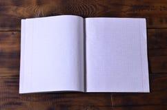 Φωτογραφία ενός καθαρού άσπρου σχολικού καρνέ επιταγών σε ένα καφετί ξύλινο υπόβαθρο Έννοια ιδέας ή μηνυμάτων Αφθονία του διαστήμ Στοκ εικόνα με δικαίωμα ελεύθερης χρήσης