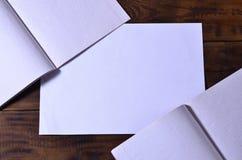 Φωτογραφία ενός καθαρού άσπρου σχολικού καρνέ επιταγών σε ένα καφετί ξύλινο υπόβαθρο Έννοια ιδέας ή μηνυμάτων Αφθονία του διαστήμ Στοκ Εικόνες