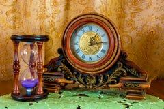 Φωτογραφία ενός παλαιού ρολογιού και sandglass στο καφετί υπόβαθρο Στοκ Φωτογραφία
