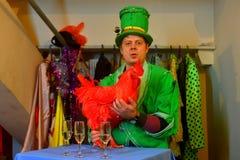 Φωτογραφία εσωτερική του καλλιτέχνη τσίρκων στα φωτεινά ενδύματα με έναν κόκκορα Στοκ εικόνα με δικαίωμα ελεύθερης χρήσης