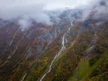 Φωτογραφία κηφήνων διάφορων μικρών καταρρακτών στα βουνά με τα σύννεφα που καλύπτουν τα κοντά στον παγετώνα Bøjabreen στη Νορβηγ στοκ εικόνα με δικαίωμα ελεύθερης χρήσης