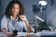 Φωτογραφία κινηματογραφήσεων σε πρώτο πλάνο της νέας γυναίκας που έχει το μολύβι στο στόμα με το τηλέφωνο κυττάρων στην εργασία Στοκ Εικόνες